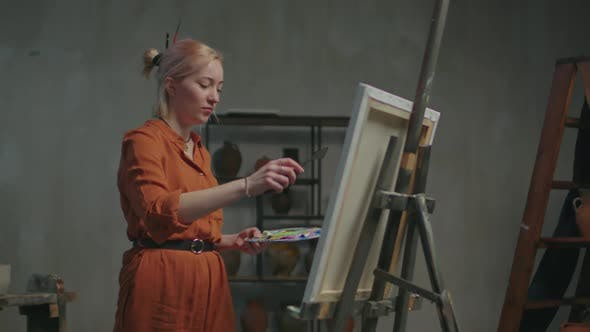 Female Artist Creating Picture Using Palette Knife