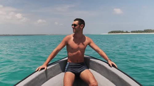 Young Successful Man in Sunglasses Enjoying on the Bow of Boat Floating By Ocean