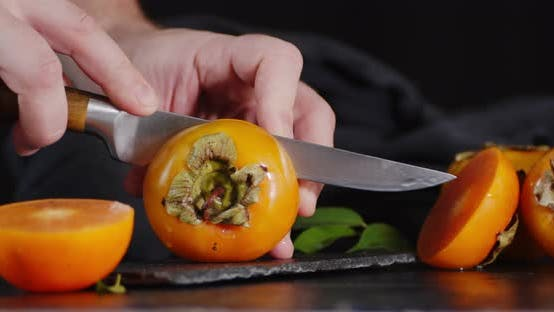 Thumbnail for Male Hand with a Knife Cut the Persimmon in Half