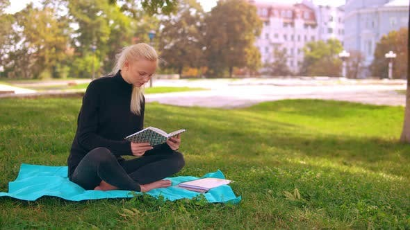 Blond Girl Reads Book in Park