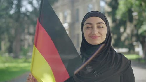 Portrait of Happy Smiling Muslim Woman Posing with German Flag on Sunny University Yard. Confident