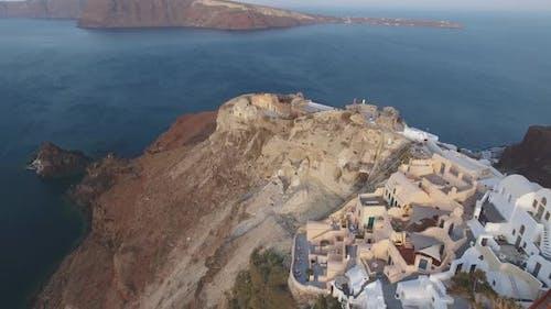 Aerial footage of Oia castle on Santorini Island in Greece during sunrise