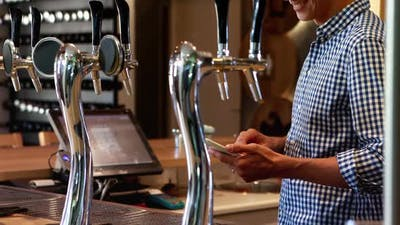 Bar tender using digital tablet at counter 4k