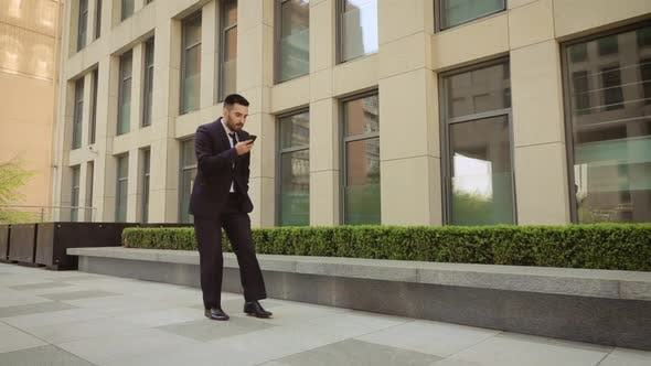 Thumbnail for Success and Achievement Happy Businessman Cheering Celebrating Looking at Cell Phone. Young Urban