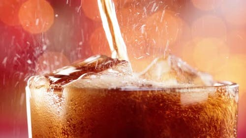 Glass of Cola. Ice Cola with Splashing Bubbles Slow Motion on a Blurry Light ,Blurry Background.