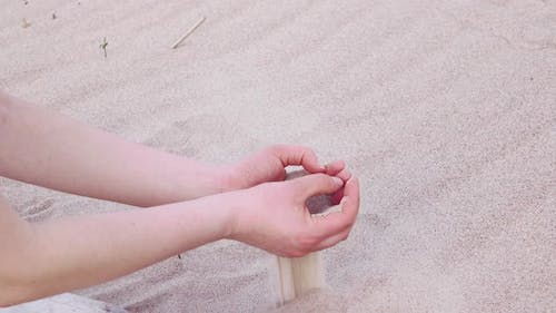 Woman's Hands Pouring Sea Sand