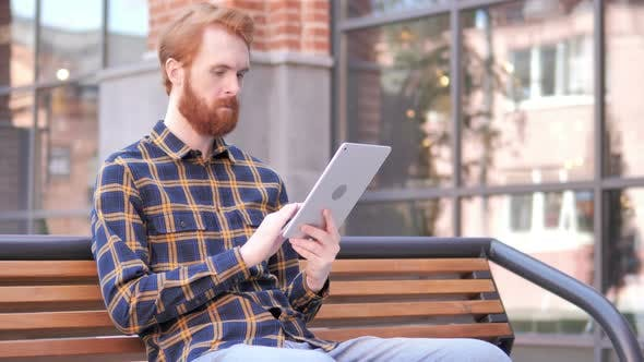 Thumbnail for Redhead Beard Young Man Using Tablet while Sitting on Bench