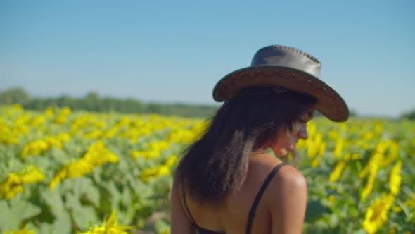 Thumbnail for Cute Black Woman in Cowboy Hat Walking in Farmland