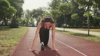 Athletic Woman Getting Ready to Start Outdoor