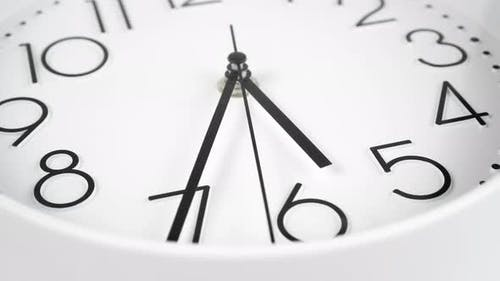 White dial of an office wall clock with black hour, minute and second hands