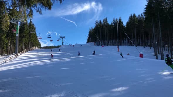 Thumbnail for People Ski Down a Snowy Hill