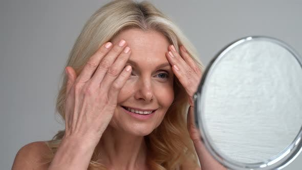 Happy 50s Middle Aged Woman Touching Face Skin Looking in Mirror