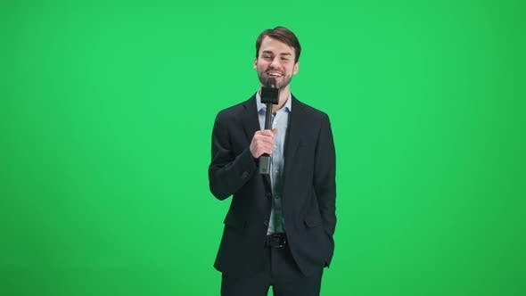 Male Reporter Looks Into the Camera and Speaks Into a Microphone on a Green Background a Template