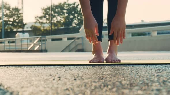 Young woman doing yoga exercise on a yoga mat at the park in summer.