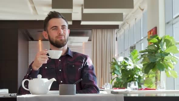 Thumbnail for Bearded Handsome Man Looking Away Thoughtfully, Enjoying Morning Tea