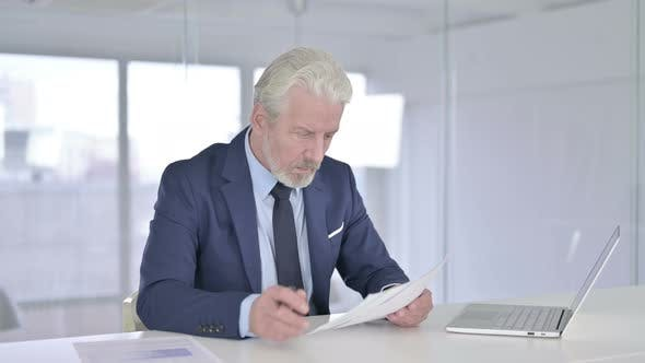 Old Businessman Reading Documents in Office