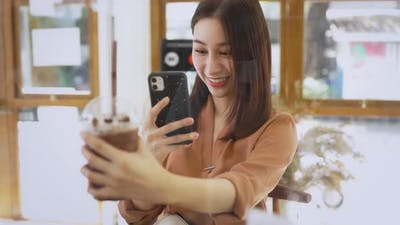 Woman Taking Selfie with Drink in Cafe