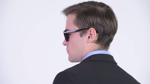 Cover Image for Rear View of Young Handsome Businessman Wearing Sunglasses and Looking Back