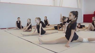 Girls Stretching Legs before Gymnastics Practice