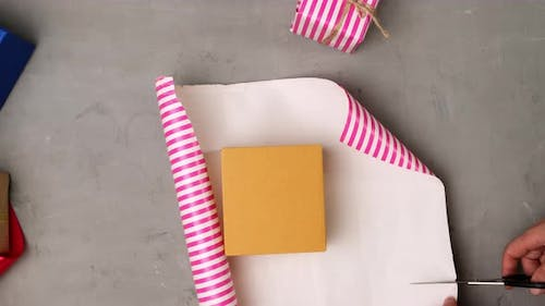 woman packing brown square box in pink paper on gray table, fruit packing process