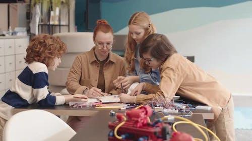 Teacher and Three Schoolchildren Drawing Robot Blueprint
