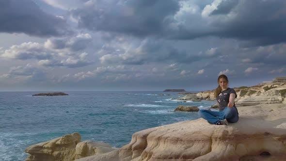 Thumbnail for Ein Mädchen sitzt auf einem Felsen auf der Meer Küste
