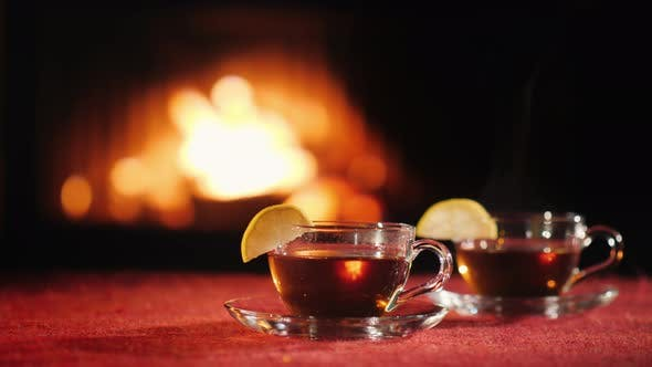 Thumbnail for Two Cups with Hot Tea on a Table with a Red Tablecloth, in the Background a Fire Burns