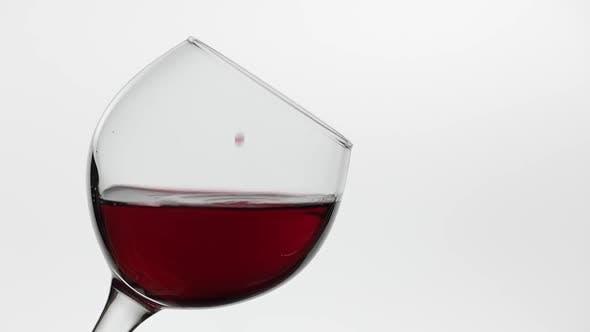 Thumbnail for Nahaufnahme eines Tropfen fallen in Glas mit Rotwein. Rosenwein auf weißem Hintergrund
