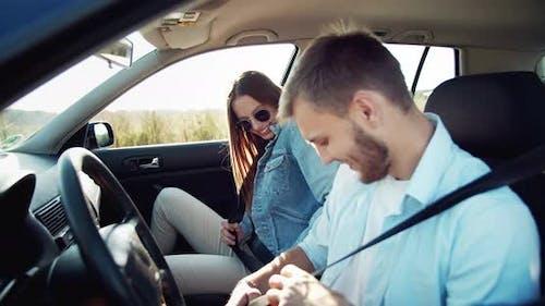 Couple Fastening Seat Belts