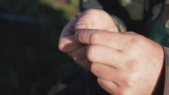 Fisherman Fixes the Earthworm on a Fishing Hook
