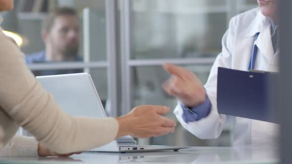 Thumbnail for Woman Giving Document and Shaking Hands with Doctor