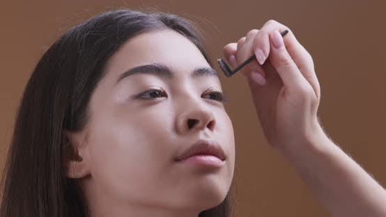 Thumbnail for Make Up Artist Doing Beautiful Eyebrows for Young Asian Girl, Close Up