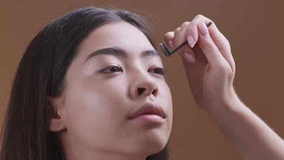 Make Up Artist Doing Beautiful Eyebrows for Young Asian Girl, Close Up