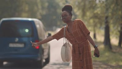 African Woman Calling Cab on Road