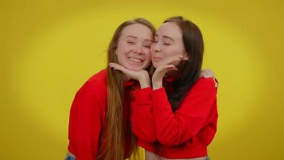 Funny Millennial Twin Sisters Grimacing Kissing Posing at Yellow Background