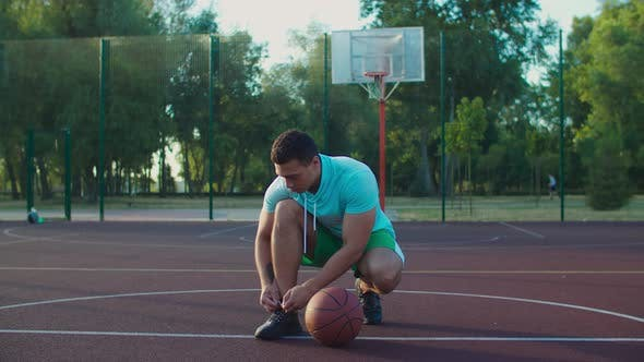 Thumbnail for Streetball Player Tying Shoe on Outdoor Court