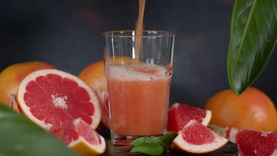 Grapefruit Juice Poured Into a Glass with Pieces of Ripe Grapefruit