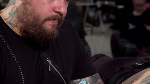 Thumbnail for Sliding Shot of a Professional Tattoo Artist Working at His Tattoo Shop