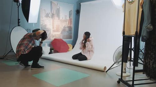 Backstage of the Photo Shoot: Black Model Sitting on the Floor and Posing for a Photographer