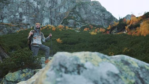 Handsome Male Hiker Standing on Rock in Autumn Mountain Forest with Trekking Poles and Heavy