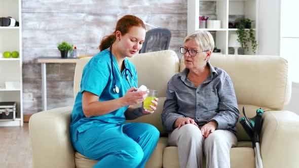 Thumbnail for weiblicher Arzt sitzt auf Sofa mit Senior Frau in Pflegeheim geben Ihr täglich Pillen