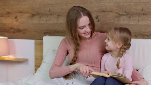 Young Mother and Child Kid Daughter Lying in Bed at Home Reading Book Bedtime Stories Fairytales