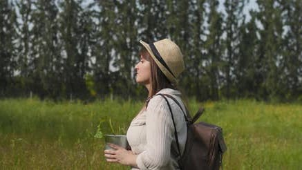 Thumbnail for Woman with hat and backpack walking through the field, carrying a pot plant.