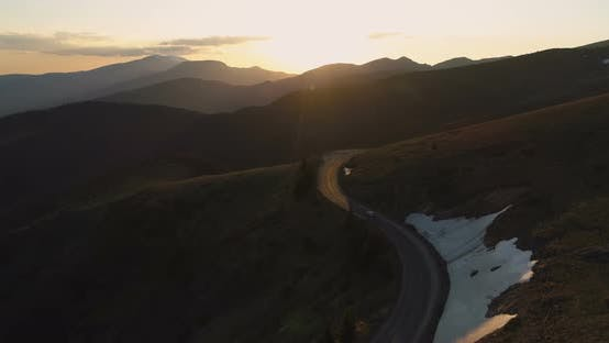 Drone Follows Lonely Car Driving on Majestic Winding Mountain Road at Golden Sunset