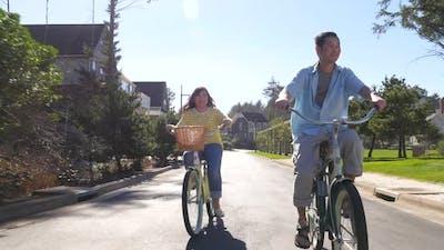 Couple riding bikes in coastal community