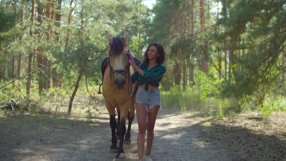 Thumbnail for Caring Horsewoman Leading Horse on Forest Trail