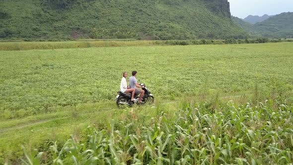 Couple Rides Scooter Along Dirty Track on Fields Upper View