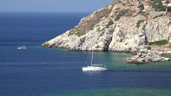 Thumbnail for A White Sailing Boat Runs Along The Rocky Coastline in The Sea