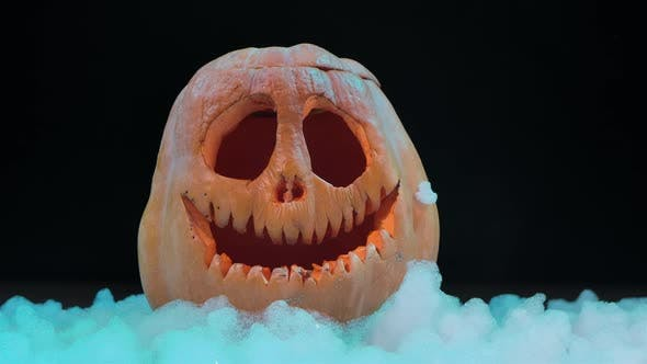Thumbnail for Funny Jack O Lantern Halloween Pumpkin in the Snow. Festive Carved Decoration of an Orange Vegetable