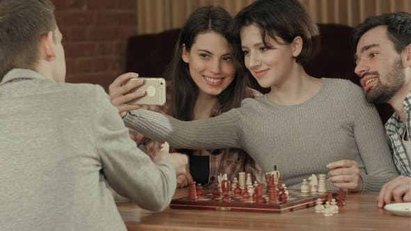 Group of students playing chess, while taking selfie photo